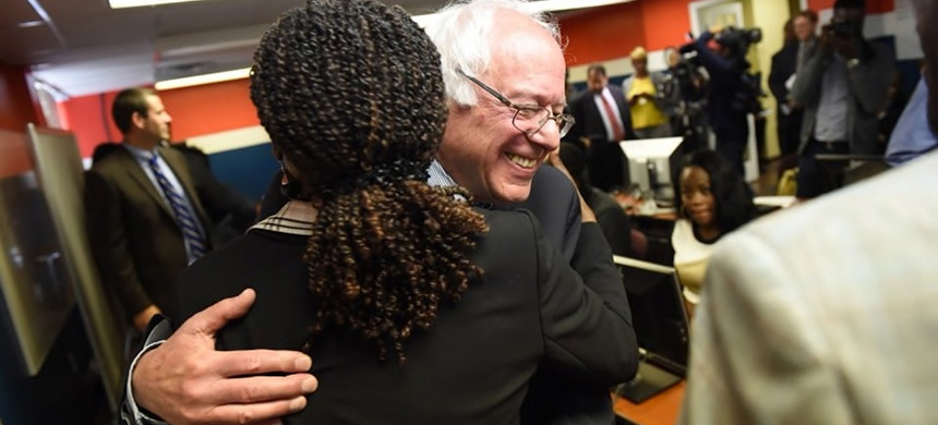 Sen. Bernie Sanders (I-Vt.) hugs a supporter after announcing a bill with Rep. John Conyers Jr. (D-Mich.) (photo: Matt McClain/AP)