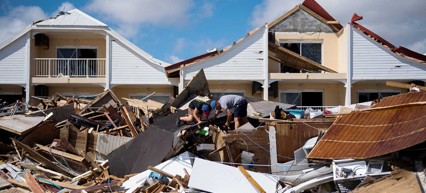 Two men search through the rubble of their St. Martin restaurant on September 10. (photo: Getty Images)