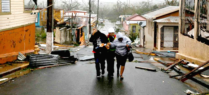 Rescue workers help people after the area was hit by Hurricane Maria in Guayama, Puerto Rico. (photo: Carlos Garcia Rawlins/Reuters)