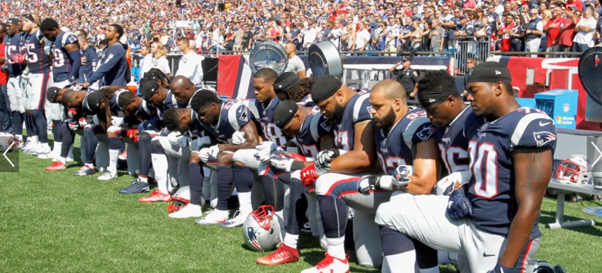 Patriot football team kneel during the US national Anthem. (photo: Getty)