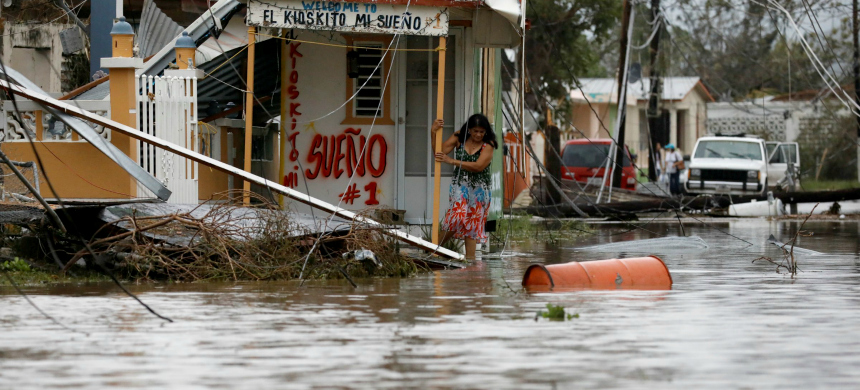 A woman tries to walk out from her house after the area was hit by Hurricane Maria in Salinas, Puerto Rico. (photo: Carlos Garcia Rawlins/Reuters)