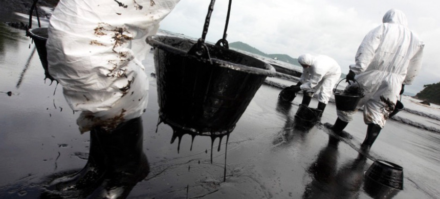 Workers attempt to clean up an oil spill. (photo: Roengrit Kongmuang/Greenpeace)