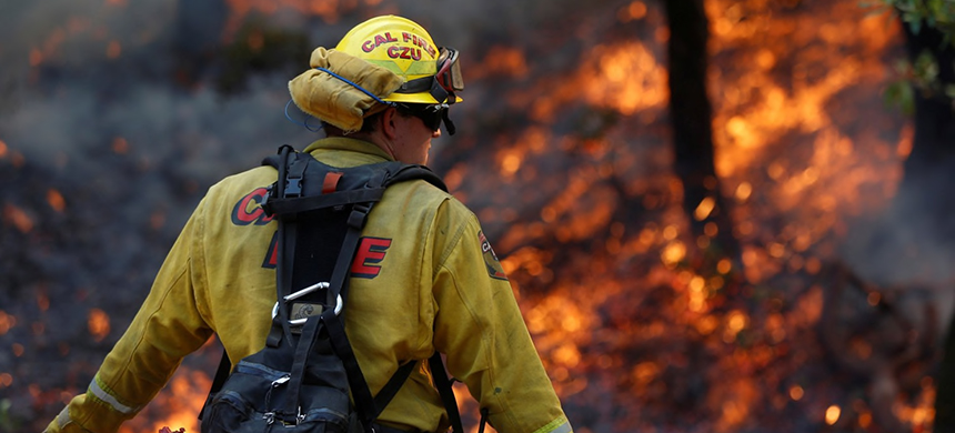 A firefighter works to defend homes from the 