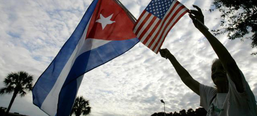 Woman holds Cuban and American flags. (photo: Reuters)