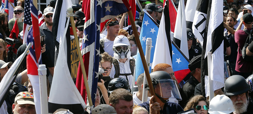 White Nationalist demonstrators walk into the entrance of Lee Park surrounded by counter demonstrators in Charlottesville, Virginia, in August of last year. (photo: Steve Helber/AP)