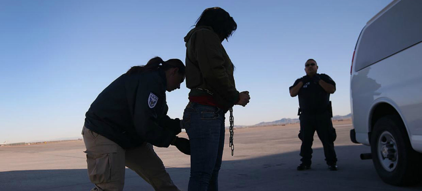 A security contractor frisks a detainee ahead of a deportation flight to Honduras. (photo: Getty Images)