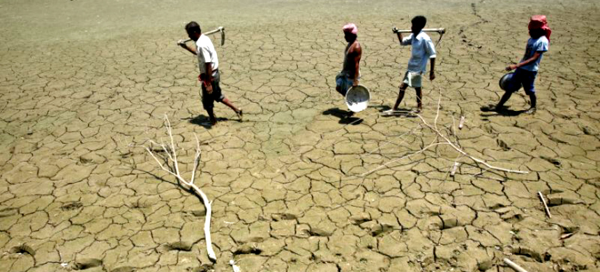 Laborers walk through a parched land of a dried lake in India. (photo: Jayanta Dey/Reuters)