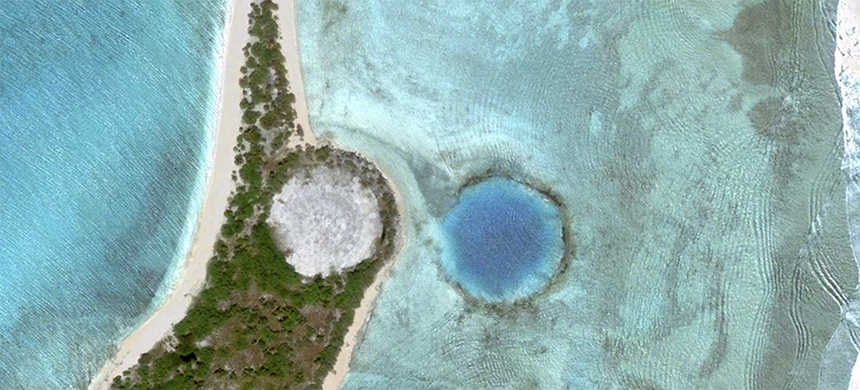 The 100-meter wide crater on Runit Island was deemed a good place to dump as much soil contaminated with plutonium as possible. Chunks of unexploded plutonium-239 were also disposed of in the hole. (photo: Google Earth)