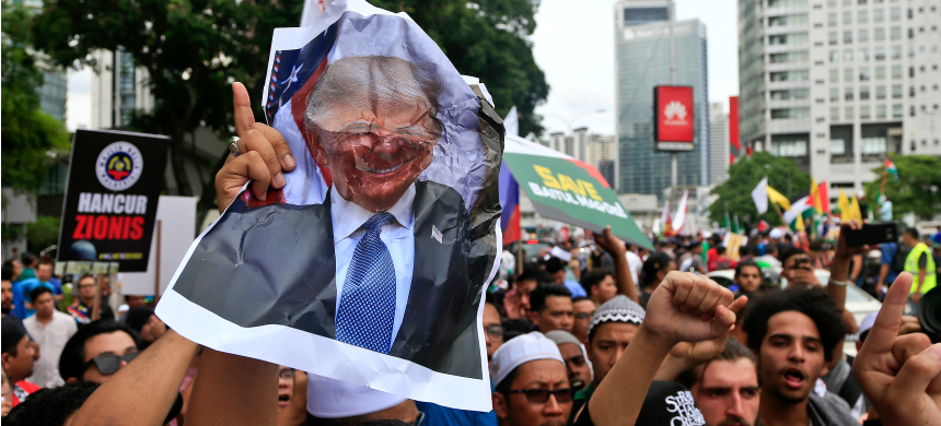 Muslims crumple a portrait of U.S. president Donald Trump during a protest outside the US Embassy in Kuala Lumpur, Malaysia, December 8, 2017. (photo: Sadiq Asyraf/AP)