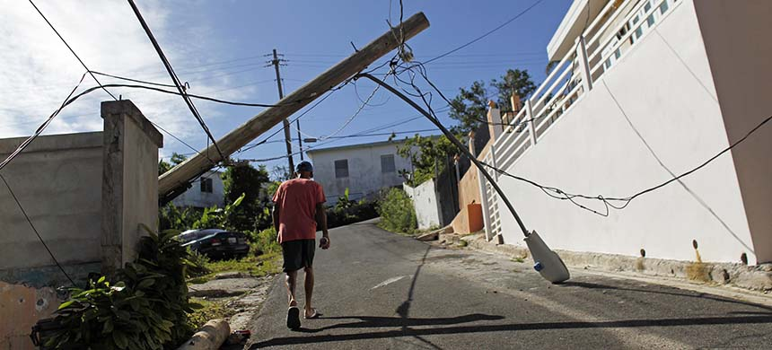 A man walks under a downed light post in Vieques, Puerto Rico. (photo: Ricardo Arduengo/NPR)