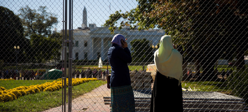 Two Muslim women stand near a fence across the street from the White House before the start of a protest against the Trump administration's proposed travel ban, October 18, 2017. (photo: Drew Angerer/Getty)