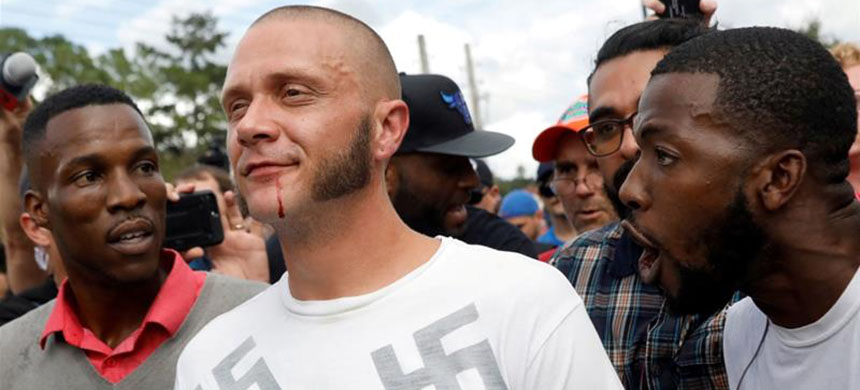 A man walks with a bloody lip as demonstrators yell at him at a far-right demonstration in Florida. (photo: Shannon Stapleton/Reuters)
