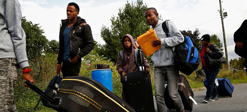 A family attempts an illegal border crossing in Champlain, New York, after they heard that Canada was accepting asylum seekers from Haiti. (photo: LA Times)