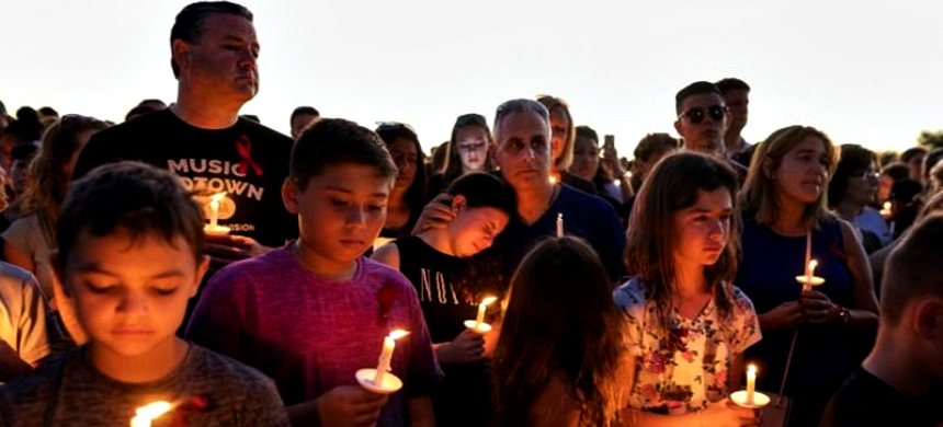 People attend a candlelit memorial service Thursday night for the victims of the shooting at Marjory Stoneman Douglas High School that killed 17 people. (photo: Greg Lovett/The Palm Beach Post)