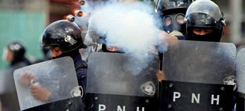 A police officer fires tear gas during clashes with demonstrators as Honduran president Juan Orlando Hernandez is sworn in for a new term in Tegucigalpa. (photo: Reuters)