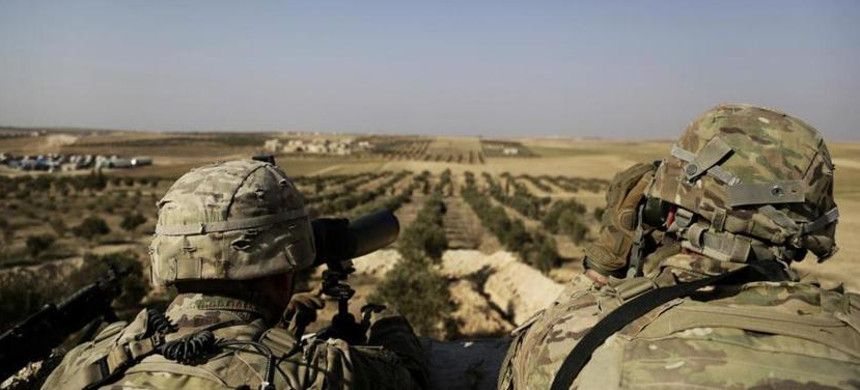 American troops look toward the border with Turkey from a small outpost in northern Syria in February. (photo: Susannah George/AP)