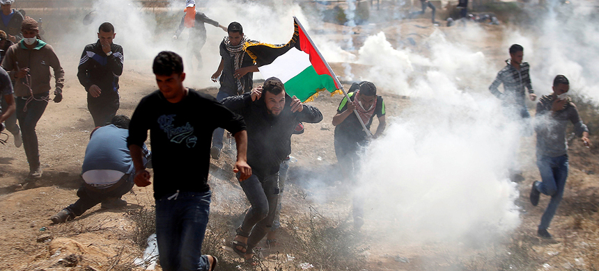 Protesters in Gaza run from Israeli tear gas. (photo: AFP)