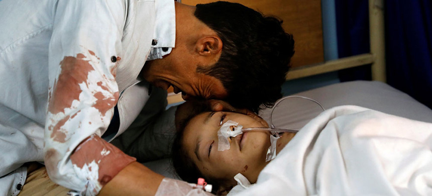 A man cries beside a wounded girl at a hospital after the attack in Kabul. (photo: Mohammad Ismail/Reuters)
