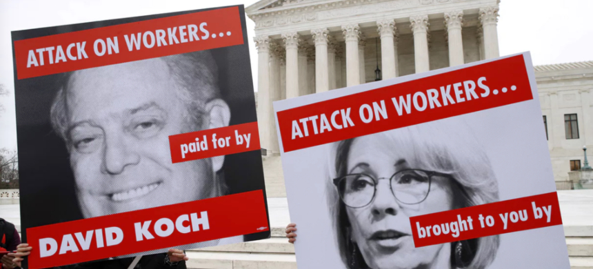 Members of the American Federation of Teachers hold up signs depicting Education Secretary Betsy DeVos and David Koch, while protesting in support of unions outside of the supreme court on 26 February. (photo: Jacquelyn Martin/AP)