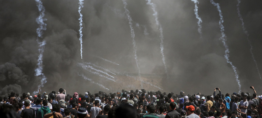 A mass attempt by Palestinians to cross the border fence separating Israel from Gaza turned deadly Monday as Israeli soldiers responded with rifle fire. (photo: Mohammed Saber/EPA)