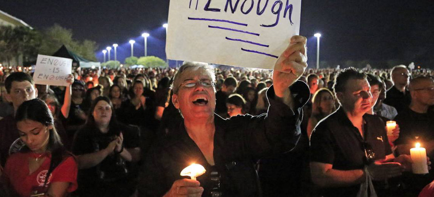 Mark Rodriguez holds a sign with #enough during a candlelight vigil at Pines Trails Park & Amphitheater for shooting victims from Marjory Stoneman Douglas High School on Tuesday, February 15, 2018. (photo: Al Diaz/Miami Herald)