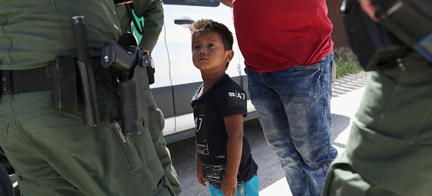 A boy and father from Honduras are taken into custody by U.S. Border Patrol agents near Mission, Texas. (photo: John Moore/Getty Images)