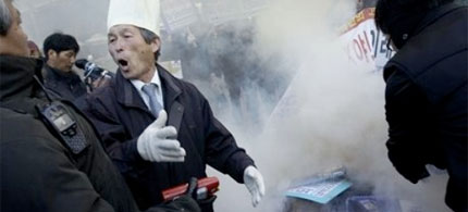 An anti-North Korea protester threatens police trying to extinguish burning icons of North Korea during a demonstration, 11/26/10. (photo: Wally Santana/AP)