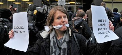 A gagged demonstrator holds placards during a protest over the arrest of the WikiLeaks founder, Julian Assange, outside the City of Westminster Magistrates' Court in central London, 12/07/10. (photo: Getty Images)