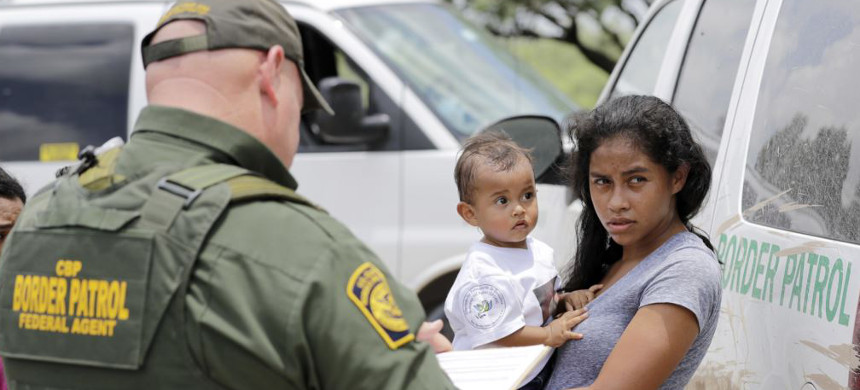 A mother migrating from Honduras holds her 1-year-old child as surrendering to U.S. Border Patrol agents after illegally crossing the border Monday, June 25, 2018, near McAllen, Texas. (photo: David J. Phillip/AP)