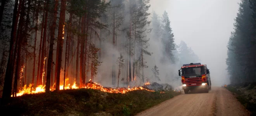 A fire vehicle is seen as fire burns in Karbole, Sweden, on July 15, 2018. The unusually hot and dry weather is helping fuel dozens of fires in the country. (photo: Mats Andersson/Getty Images)