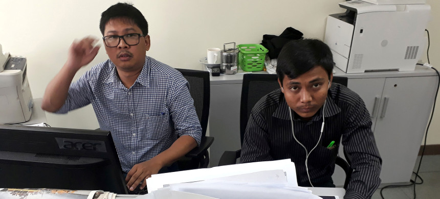Wa Lone (left) and Kyaw Soe Oo typing up notes in the Reuters office in downtown Yangon on December 11, one day before their arrests. (photo: Antoni Slodkowski/Reuters)