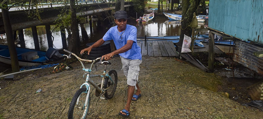 Fisherman Jimmy Lalla, 36, moves a bike at his home near the water in Woodland, Trinidad. He and the first mate on their fishing vessel fled a pirate attack by jumping overboard; the boat's captain was kidnapped and is still missing. (photo: WP)