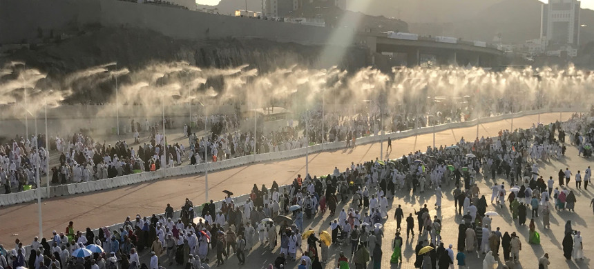 Participants in the hajj pilgrimage in Mecca walk down a road with a water spray cooling system, part of an increasingly sophisticated support system required to cope with the heat. (photo: Getty)
