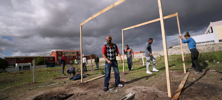 South Africans erecting a shack during illegal land occupations in a township near Cape Town. A proposed change in a land ownership law has become a highly divisive issue. (photo: Mike Hutchings/Reuters)