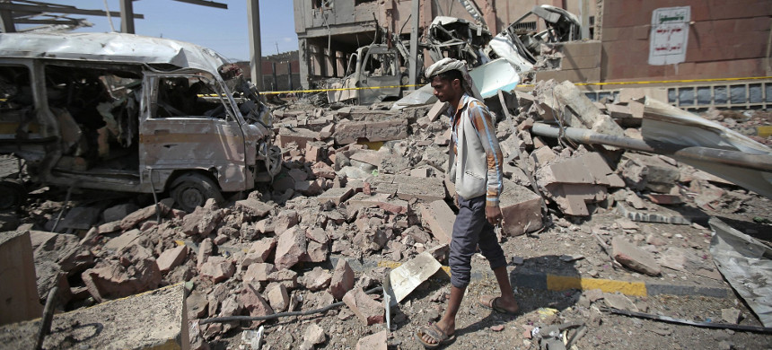 A man inspects rubble after a Saudi-led coalition airstrike in Sanaa, Yemen. (photo: Getty)