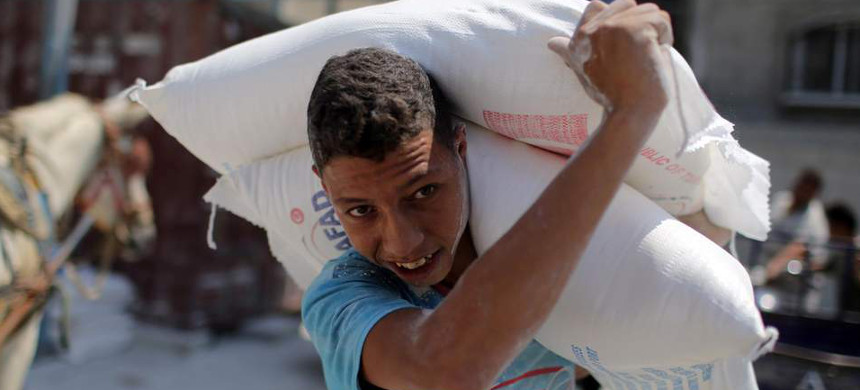 A Palestinian child carries humanitarian food aid. (photo: Reuters)