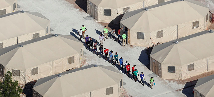 Migrant youth walk in a line. (photo: Mike Blake/Reuters)