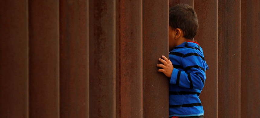 A child peeks through the border fence in Ciudad Juarez, Mexico, last month. (photo: Jose Luis Gonzales/Reuters)