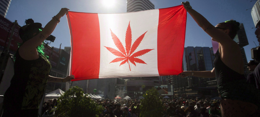 Two people hold a modified design of the Canadian flag with a marijuana leaf in in place of the maple leaf during the '420 Toronto' rally in Toronto, April 20, 2016. (photo: Mark Blinch/CP)