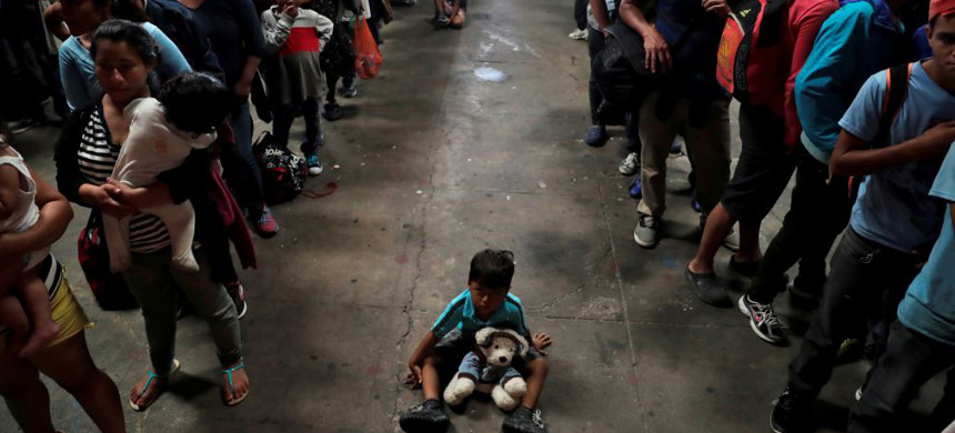 A child sits on the floor as Honduran migrants, part of a caravan trying to reach the U.S., queue to get a mat to rest at a migrant shelter in Guatemala City, Guatemala, October 17, 2018. (photo: Reuters)