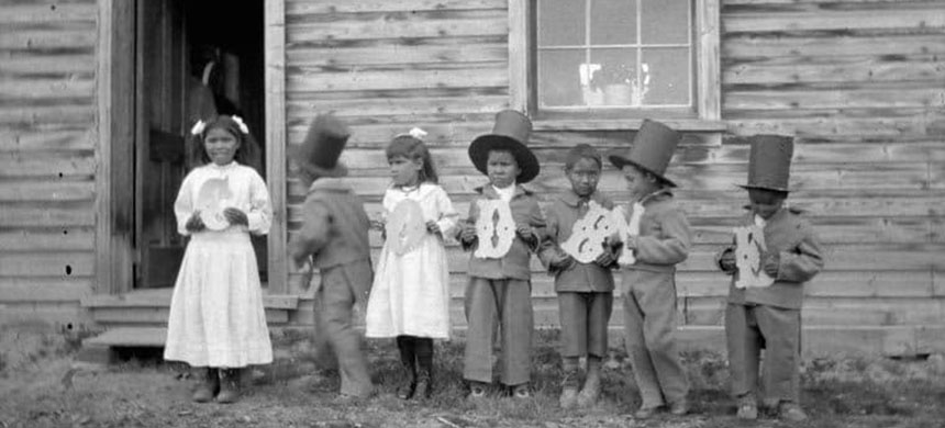 Indigenous children hold letters that spell 'goodbye' at Fort Simpson Indian Residential School in the Northwest Territories in this undated photo. (photo: J.F. Moran/Library and Archives Canada)