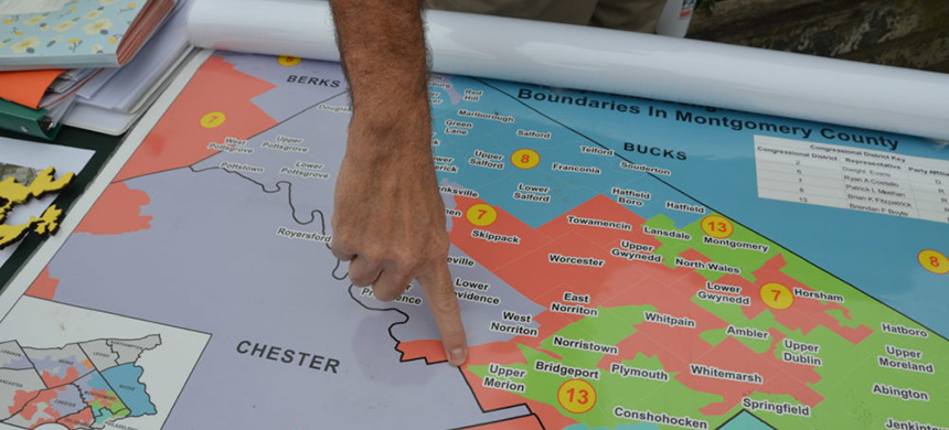 A man points to a Congressional district map of boundaries in Montgomery County, Pennsylvania. (photo: WBUR)