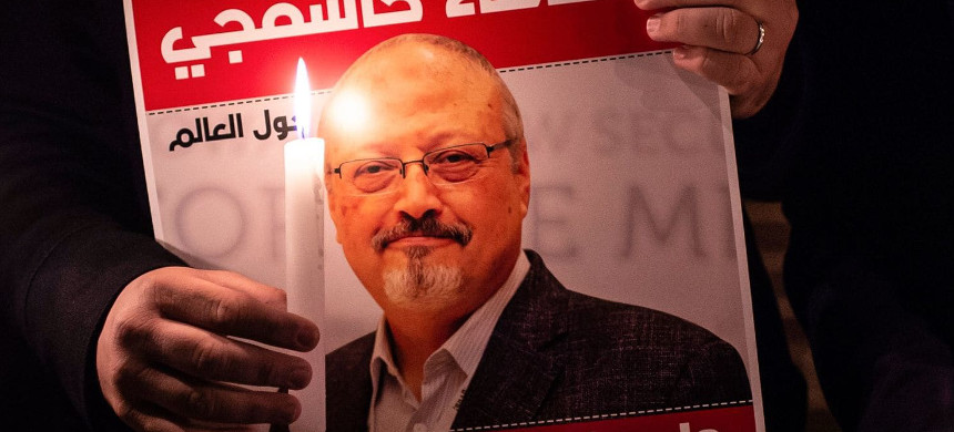 A demonstrator holds a poster picturing Saudi journalist Jamal Khashoggi and a lightened candle during a gathering outside the Saudi Arabia consulate in Istanbul. (photo: Yasin Akgul/AFP)