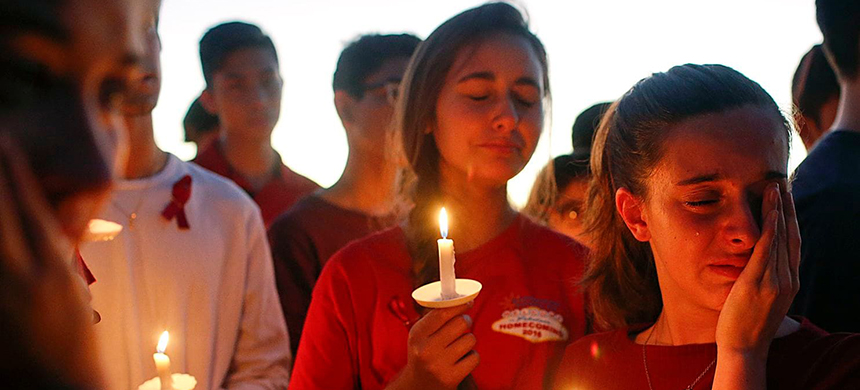 Students grieve at a vigil in Parkland, Fla., a day after the shooting at Marjory Stoneman Douglas High School. (photo: Brynn Anderson/AP)