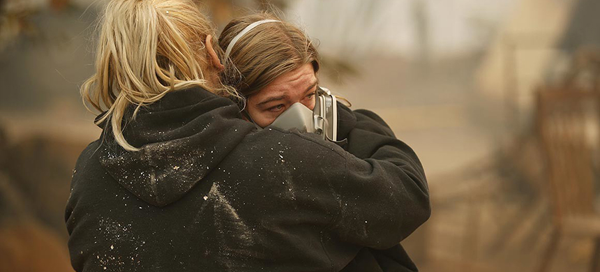 Krystin Harvey (left) comforts her daughter, Araya Cipollini, at the remains of their home burned in the fire Saturday in Paradise, California. (photo: John Locher/AP)