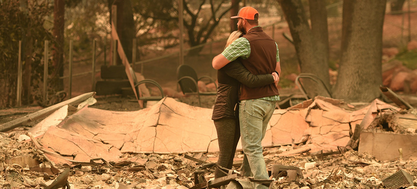 Chris and Nancy Brown embrace Monday while looking over the remains of their burned residence after the Camp Fire tore through the region in Paradise, Calif. (photo: Josh Edelson/AFP/Getty Images)