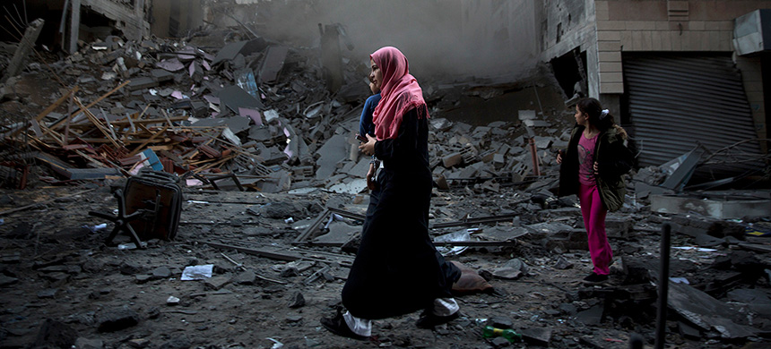 A Palestinian family walks next to a destroyed residential building hit by Israeli air attacks in Gaza City on Tuesday. (photo: Khalil Hamra/AP)