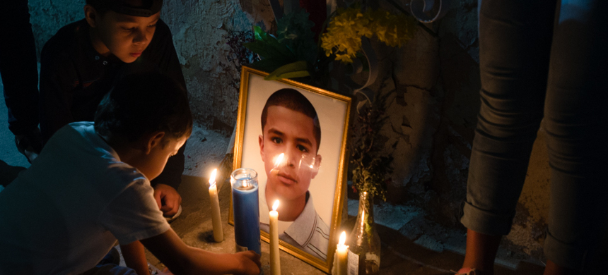 Family of Jose Antonio Elena Rodriguez, a Mexican teenager killed in a cross-border shooting by a US Border Patrol agent, light candles in front of his portrait. (photo: Paul Ingram/TucsonSentinel)