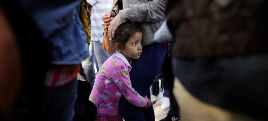 Nicole Hernandez, of the Mexican state of Guerrero, holds on to her mother as they wait with other families to request political asylum in the United States, across the border in Tijuana, Mexico. (photo: Gregory Bull/AP)