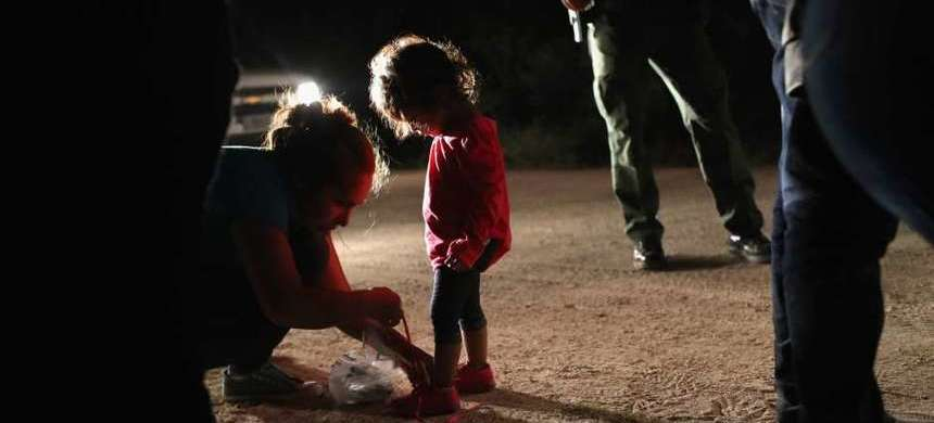 A Honduran mother removes her two-year-old daughter's shoe laces, as required by U.S. Border Patrol agents, after being detained near the U.S.-Mexico border on June 12 in McAllen, Texas. (photo: John Moore)